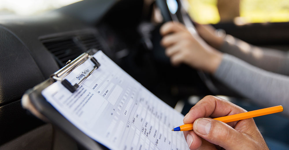 Driving test instructor holding clipboard with pencil representing on-road impairment testing