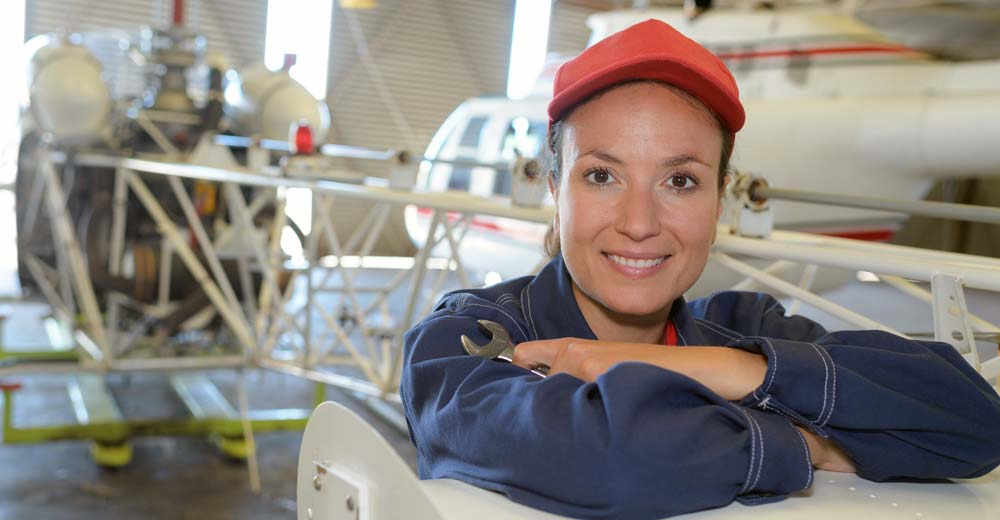 Woman airplane mechanic smiling representing workplace occupational health and safety