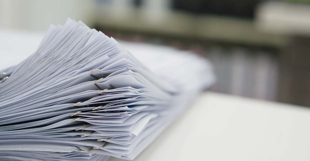Stack of white paper on a desk representing research